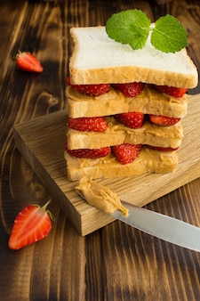 Big sandwich with strawberry and peanut butter on the kitchen board on the brown wooden background. vertical location.