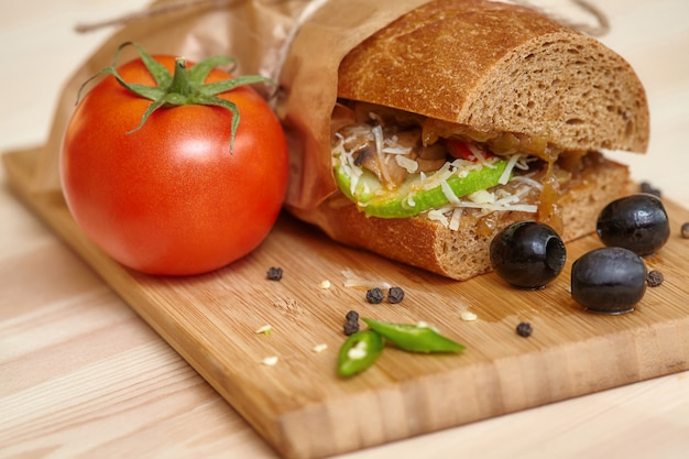 Big sandwich on wooden cutting board with ingridients