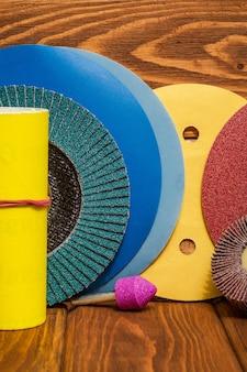 Большой набор абразивных инструментов и разноцветной наждачной бумаги на деревянном винтажном фоне, мастер используется для шлифовки предметов