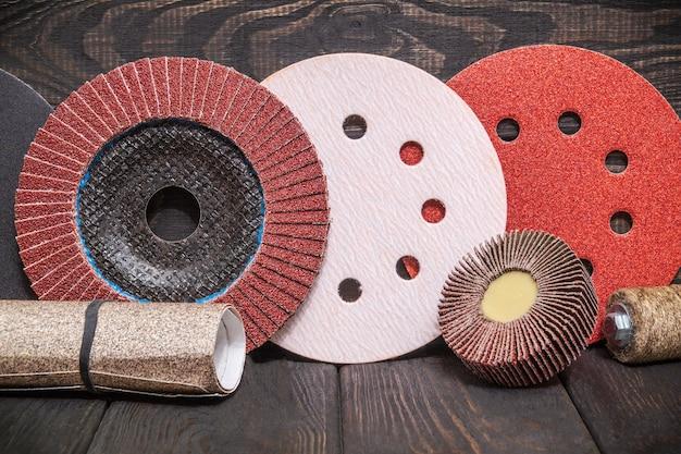 Большой набор абразивных инструментов и разноцветной наждачной бумаги на деревянном винтажном черном фоне, мастер используется для шлифовки предметов