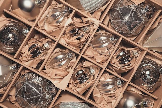 豪華なシルバーガラスのつまらないものの大きなセット。ボックス内のヴィンテージのクリスマスの装飾のレトロなスタイルのイメージ。