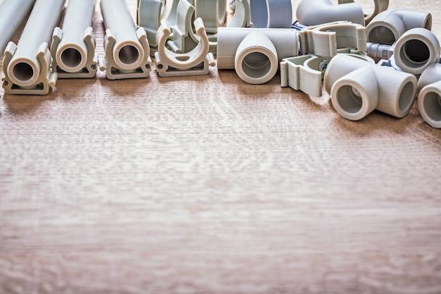 Big set полипропиленовые фиксаторы и трубы с зажимами фитинги крупным планом вид на деревянную доску