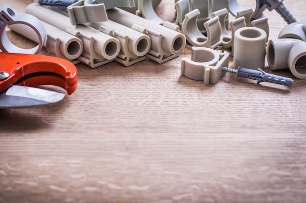 Фиксаторы и трубы полипропилена большого комплекта с резцом трубы зажимов на деревянной доске