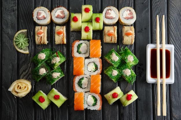 Big set of rolls, soy sauce and chopsticks (hashi) on dark