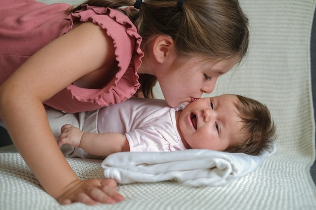 Big sister kiss little happy baby girl on couch. happy family. at home. love. sweet. tenderness. big sister. slow motion