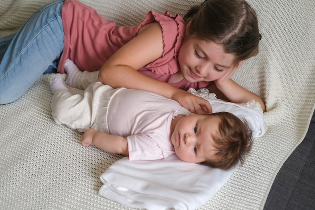 Big sister play with little happy baby girl on couch. happy family. at home. love. sweet. tenderness. big sister. slow motion