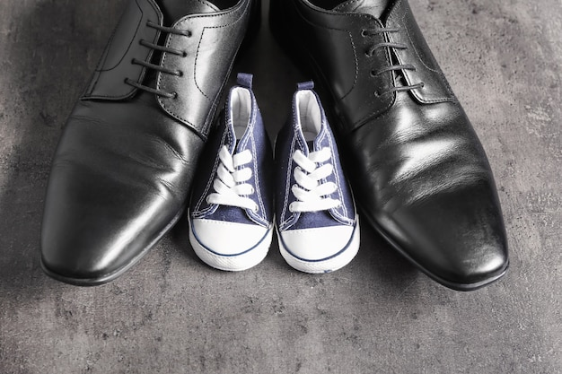 Big and small shoes on grey table. father's day celebration