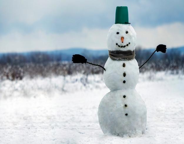 バケツ帽子、スカーフ、白い雪原の冬の風景、ぼやけた黒い木と青い空コピースペース背景に手袋と大きな笑みを浮かべて雪だるま。 。メリークリスマスと幸せな新年のグリーティングカード。