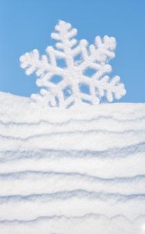 Большая игрушка снежинка на голубом небе