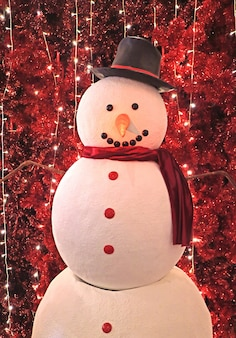 Big snowman in front of sparkling artificial red pine trees for christmas