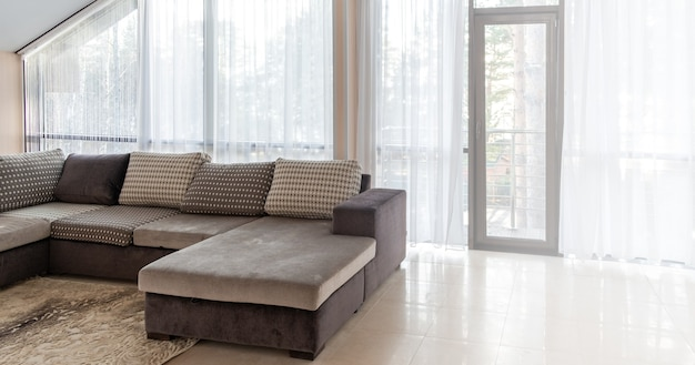 Big sofa and large windows interior design with morning sunlight from the outside