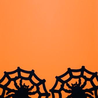 オレンジ色のクモの巣と大きなクモ