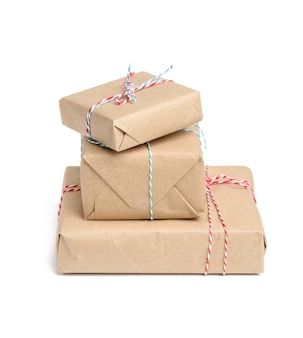 Big stack of gifts wrapped in brown kraft paper and tied with rope, boxes isolated on white background, element for designer