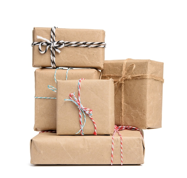 Big stack of gifts wrapped in brown kraft paper and tied with rope, boxes isolated on white