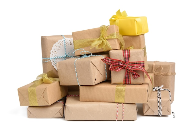Big stack of gifts wrapped in brown kraft paper and tied with silk ribbon