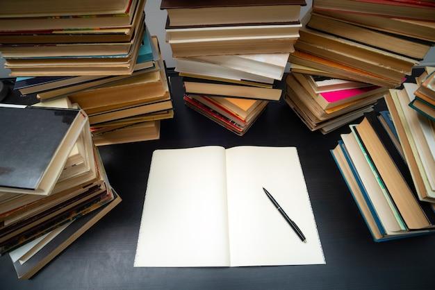 Большая стопка книг на столе. учеба перед экзаменом. куча старинных книг. концепция образования и обучения