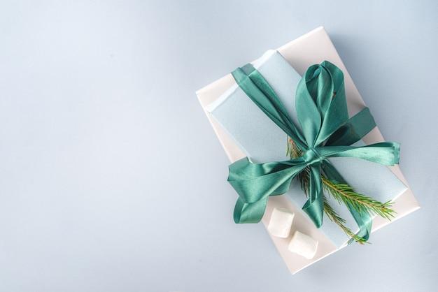 ホットチョコレートとクリスマスプレゼントの大きなスタック、台座のようにその上にとどまる、緑のお祝いのクリスマスリボンが付いた居心地の良いパステルカラーのクラフト紙ギフトボックス、マシュマロとココアのカップ、コピースペース