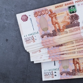 Big stack of russian money banknotes of five thousand rubles lying on a grey cement.