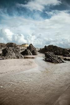 낮 동안 해변에 큰 돌과 젖은 모래