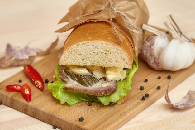 Биг сэндвич с ветчиной на деревянной разделочной доске