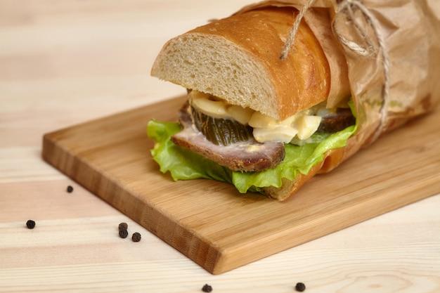 Большой сэндвич багет с ветчиной на деревянной разделочной доске