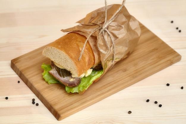 Big sub sandwich baguette with ham on wooden cutting board