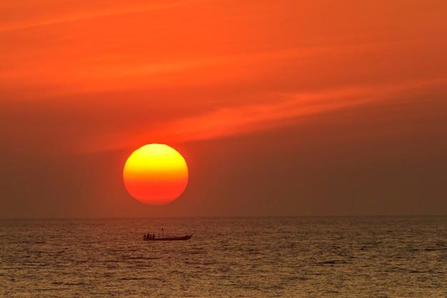 Большое солнце над лодкой на море
