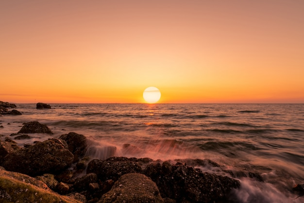 Big sun on skyline at sunset. ocean water splash on rock beach with beautiful sunset sky and orange clouds. sea wave splashing on stone at sea shore on summer. nature landscape. tropical seascape.
