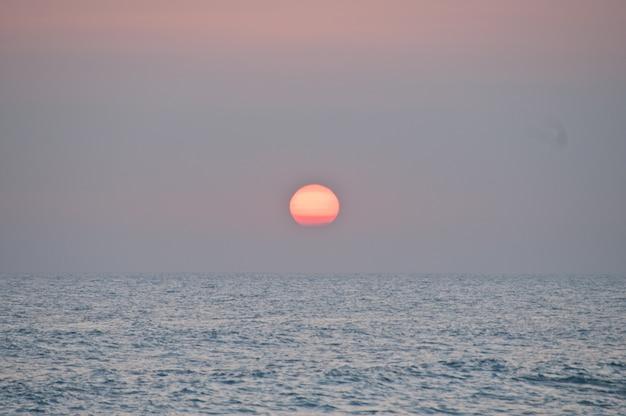 Большой закат до спокойного моря на бали на пляже танах