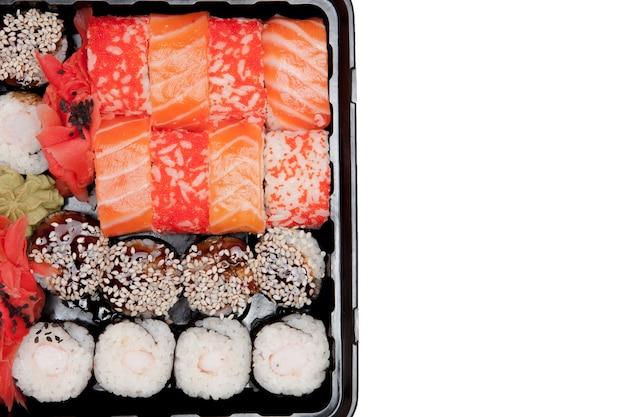 白い背景に大きな寿司セットib黒いプラスチックの箱、上面図のクローズアップ、コピースペース。