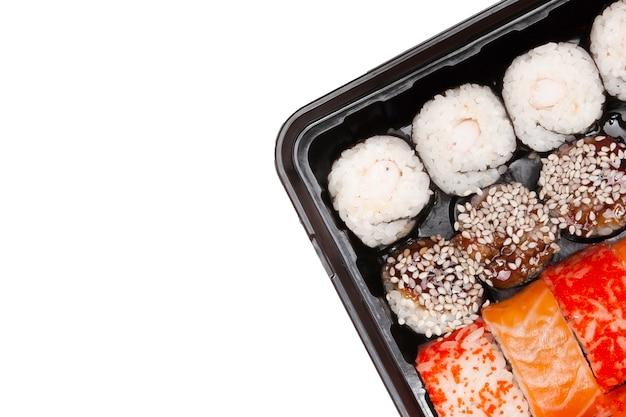 Большой набор суши ib черная пластиковая коробка на белом, вид сверху крупным планом, копией пространства