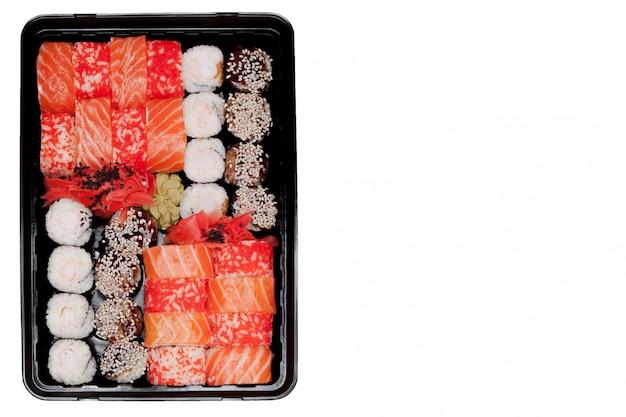 Big sushi set ib black plastic box on white background, top view close up, copy space