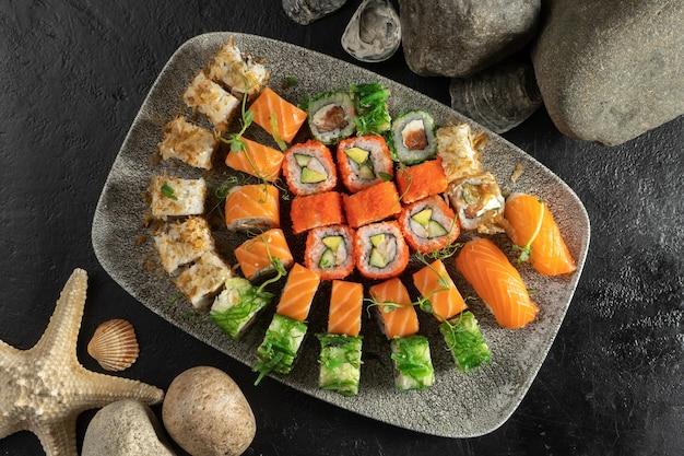Big sushi set. sushi rolls and nigiri with salmon, avocado, tobiko caviar, tuna flakes, chuka salad.