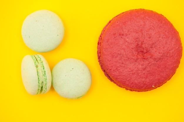 黄色の背景の上の小さなマカロンの横にある大きな甘いラズベリーマカロン。贅沢なデザート
