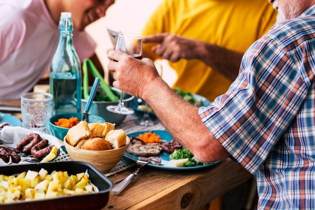 식생활 빵, 고기, 야채로 가득한 큰 테이블... - 테이블 옆에 앉아 포도나무와 물을 먹고 마시는 사람들 - 축하 - 많은 샐러드와 모든 종류의 음식