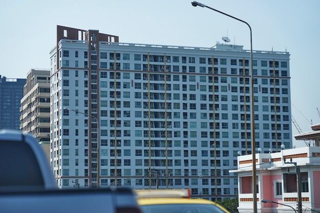 空を背景に街の景色を望む大きな高層ビルのコンドミニアムは、車の前景をぼかす