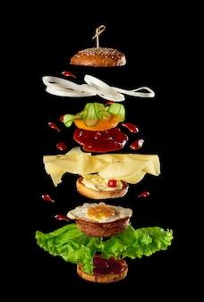 Большой вкусный бургер с мясной котлетой, сыром, жареным яйцом, помидорами, кусочками огурца и зеленым салатом, фаст-фуд левитирует, черный фон