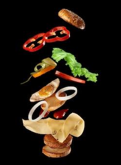 Большой вкусный бургер с мясной котлетой, сыром, жареным яйцом, помидорами, кусочками огурца и зеленым салатом, фастфуд левитирует, черный фон