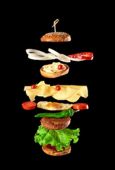 Big tasty burger with meat cutlet, cheese, fried egg, tomatoes, cucumber pieces and green lettuce, fast food levitatesba