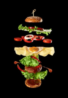 Big tasty burger with meat cutlet, cheese, fried egg, tomatoes, cucumber pieces and green lettuce
