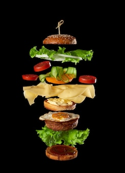 Big tasty burger with meat cutlet, cheese, fried egg, tomatoes, cucumber