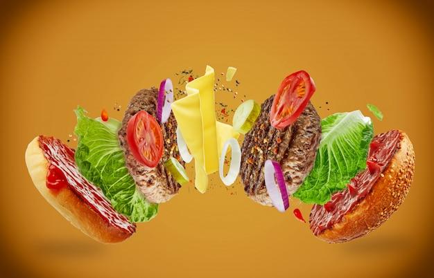 茶色の背景に食材が飛んで大きなおいしい自家製ハンバーガー。食品浮上の概念