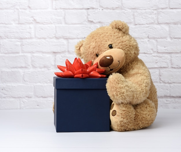Big teddy bear and blue square cardboard box with red bow