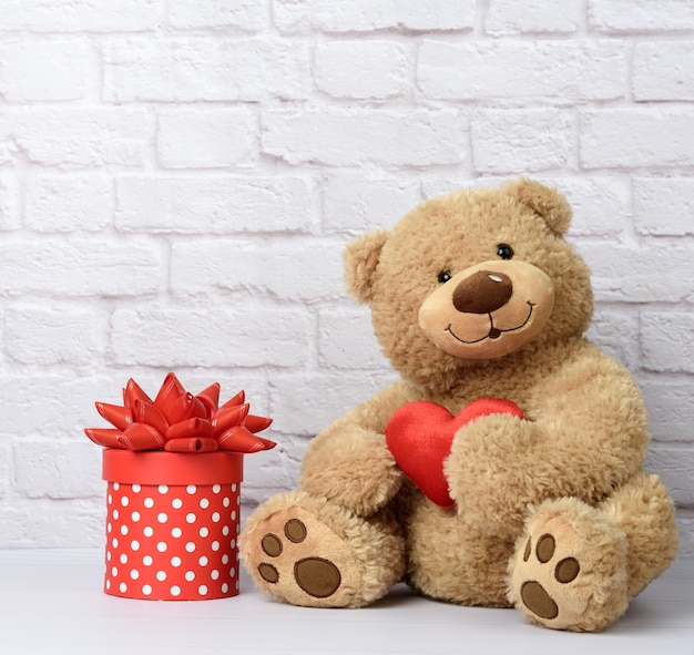 Big teddy bear and cardboard box with red bow on white brick wall background