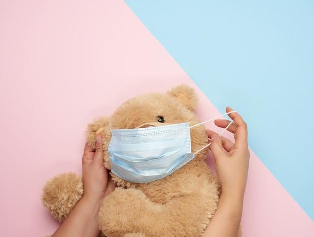 Большой плюшевый мишка в медицинских масках на сине-розовом