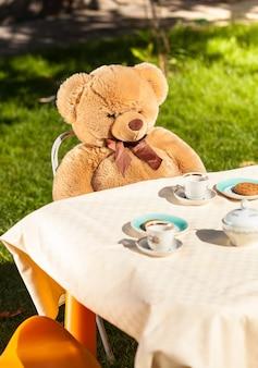 テーブルの後ろに座ってお茶を飲む大きなテディベア