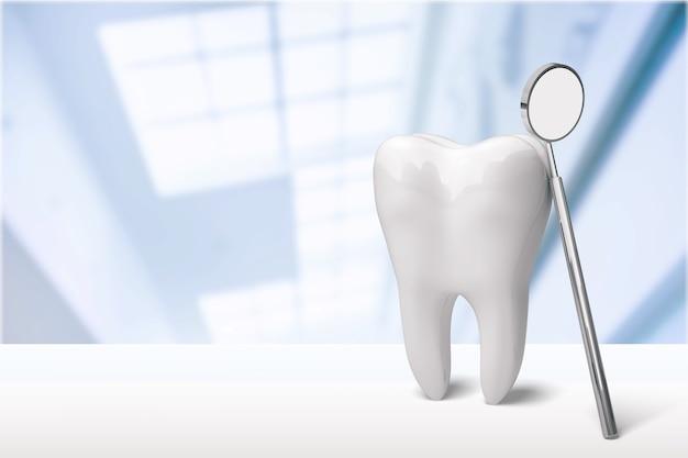 背景の歯科医院の大きな歯と歯科医の鏡