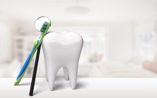 背景の大きな歯のモデルと歯ブラシ