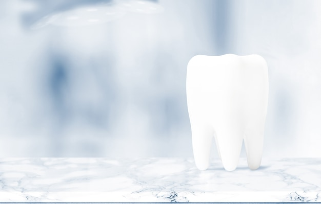 Big tooth on table in dentist clinic on background