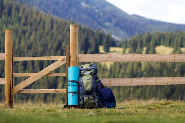 Big tourist backpack and a small one leaned at low wooden fence on lit by sun grassy valley on mountains covered with dense forest blurred background. tourism, camping and traveling concept.